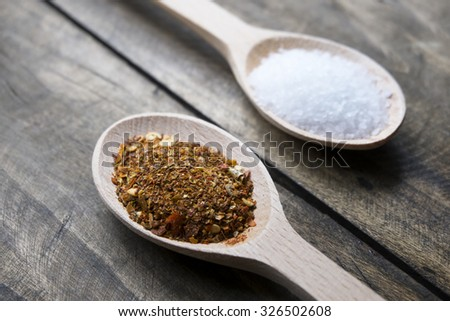 Red pepper flakes in wooden spoon, close up - stock photo