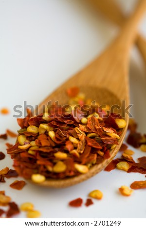 red pepper flakes on a wooden spoon over following