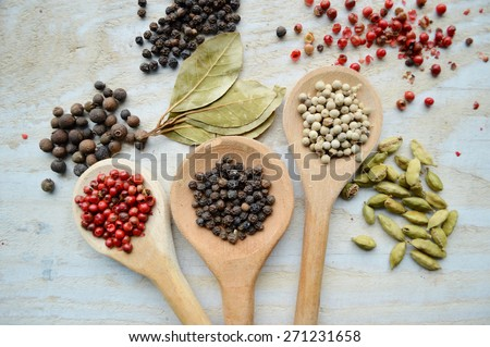 red pepper peas,black pepper peas,white pepper corns,a Bay leaf,cardamom on wooden background - stock photo