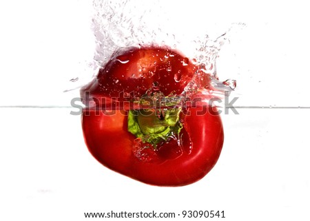 Red pepper plunging in water - stock photo