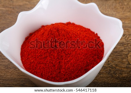 Red pepper powder heap in the bowl over wooden background