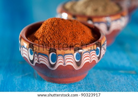 Red pepper, salt and savory in traditional bulgarian ceramic bowls on blue background