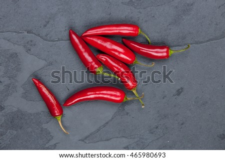Red peppers on a grey cutting board, stock picture