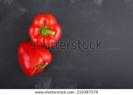 Red Peppers on dark chalkboard with copy-space - stock photo