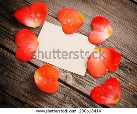 red petal with paper on wooden background - stock photo