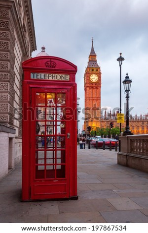 red phone box in front of the Big Ben in London at dusk - stock photo