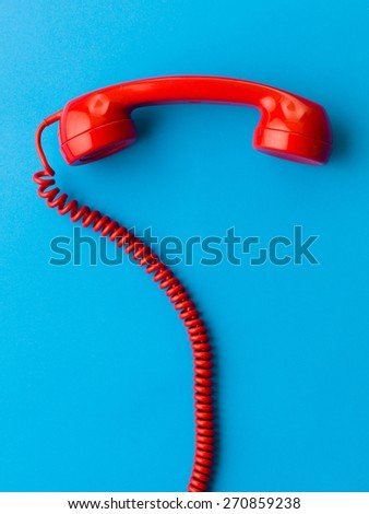 red phone receiver on blue background - stock photo