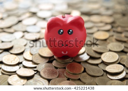 red piggy bank on coins background