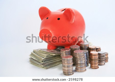 Red piggy bank on top of stacks of money coins and dollars side view