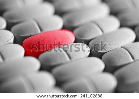 Red pill in row of monochrome pills. Macro image. - stock photo