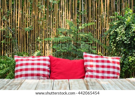 Red pillows on a wooden table in out door patio with golden bamboo curtain background. - stock photo