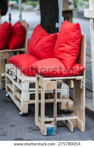 Red pillows sitting on a bundle of wooden parts