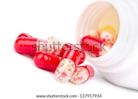 Red pills an pill bottle - stock photo