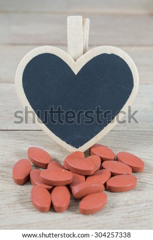 Red pills  with blank heart shape blackboard on wood background