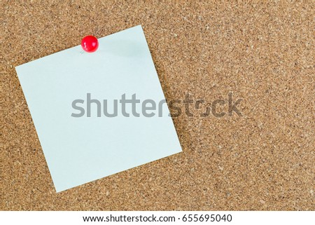 red pin on note paper with cork board background