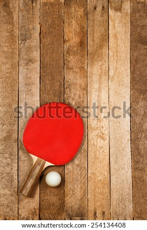 Red ping pong paddle and ball on vintage wooden background - stock photo