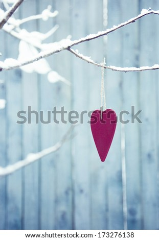 red pink heart hanging on the tree with a lot of snow and a fence on the background. Romantic atmosphere. - stock photo