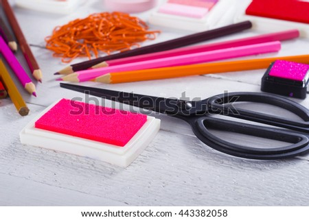 red, pink, purple color pencils and paper clips, ink pads on white wooden table background - stock photo