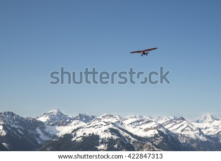 red plane flying over the alps