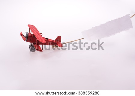 Red plane flying with a paper after it on a white background - stock photo