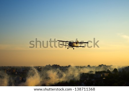 Red plane spraying mosquitoes over European town of Osijek, Croatia - stock photo