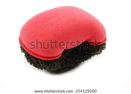 red plastic and foam abrasive pad on a white background - stock photo