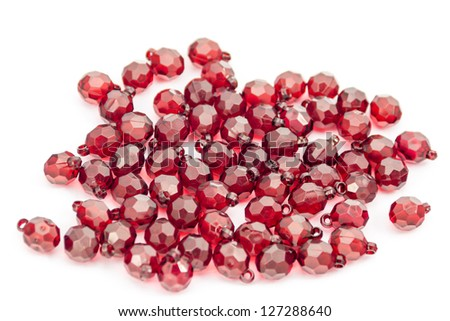 Red plastic beads closeup on white background - stock photo