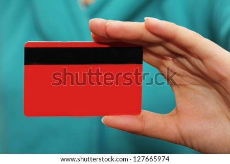red plastic card in hand - stock photo