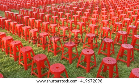 Red plastic chairs at an open air event ground. - stock photo