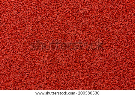 Red plastic doormat texture and background - stock photo