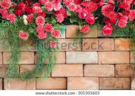 red plastic flowers on the brick wall
