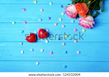 Red plastic hearts and roses on blue  wooden background