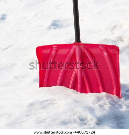 Red plastic shovel for snow removal. Closeup. - stock photo