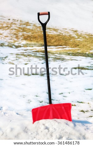 Red plastic shovel for snow removal. Winter is coming. - stock photo