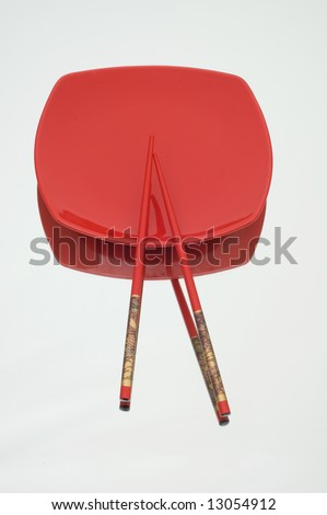 Red plate and chopsticks on reflective background