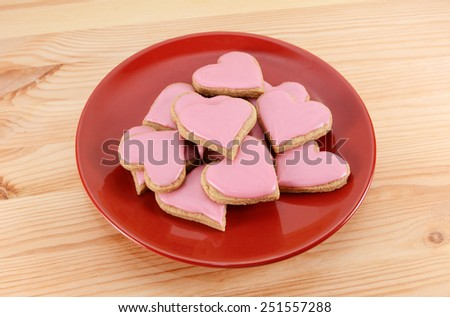 Red plate stacked high with frosted heart-shaped cookies for Valentine's Day, on a wooden table