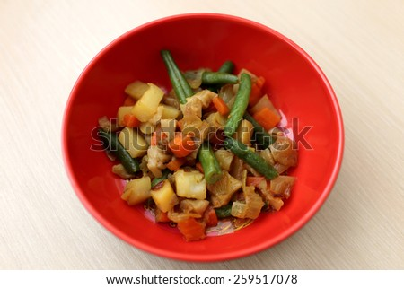 Red plate with vegetable stew on a wooden table - stock photo