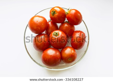 Red plum tomatoes in glass bowl on white background, top view