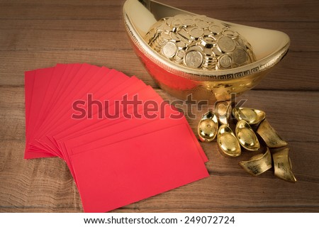 Red pocket and ancient Chinese golden ingots on wooden : with copyspace