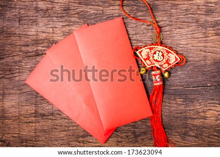 Red pocket and Chinese red tassel on wooden table top - stock photo