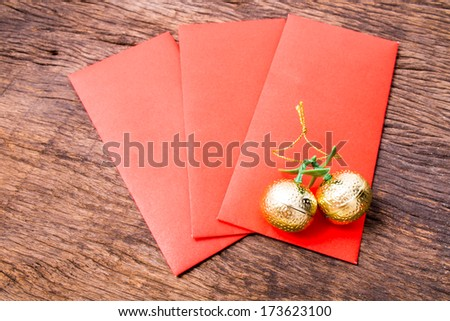 Red pocket and golden oranges on wooden table top - stock photo