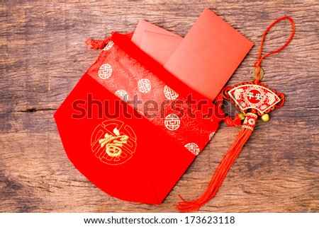 Red pocket in Chinese red bag and Chinese red tassel on wooden table top - stock photo