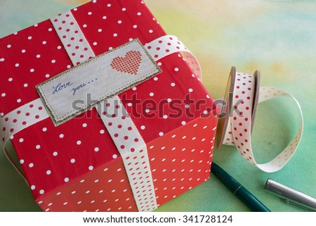 Red polka dot gift box with ribbon and label with the message Love you