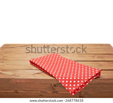 Red polka dot tablecloth or towel over the surface of a brown wooden table, composition isolated over the white background - stock photo