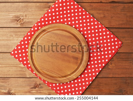 Red polka dot tablecloth or towel over the surface of a brown wooden table with a round wooden tray on top of it - stock photo