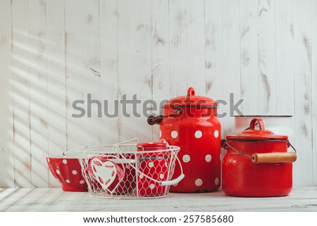 Red polka dot vintage kitchen utensils on a white talbe - stock photo