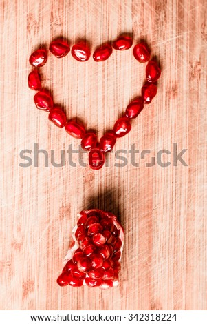 Red pomegranate fruit. Ripe vegetarian food. Heart of sweet juicy fresh organic seed wood background. Healthy raw closeup tropical half piece with juice. Tasty antioxidant dessert. Vintage effect - stock photo