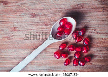 Red pomegranate fruit. Ripe vegetarian food. Sweet juicy fresh organic seed and spoon on wood background. Healthy raw closeup tropical half piece with juice. Tasty dessert. Vintage effect - stock photo
