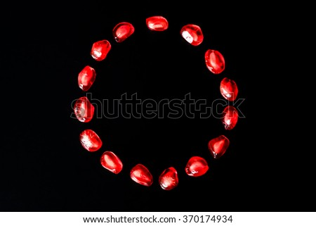 Red pomegranate fruit. Ripe vegetarian food. Sweet juicy fresh organic seed isolated on black background. Healthy raw closeup tropical half piece with juice. Tasty antioxidant dessert. - stock photo
