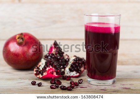 Red pomegranate juice in a glass, near a fruit pomegranate and half of pomegranate on wooden background